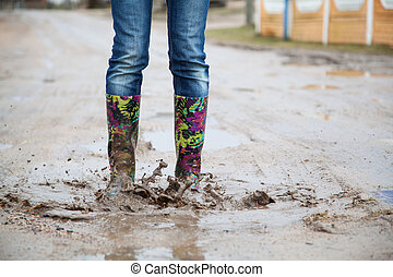 Woman with rain boots jumps