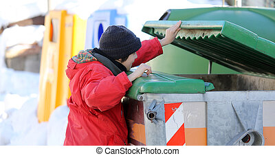 poor young boy tries to eat into the waste box in winter