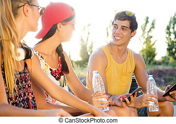 Group of friends texting with their smart phones in the park...