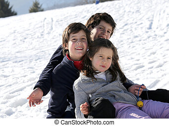 three smiling siblings over the sled in winter in the mountains
