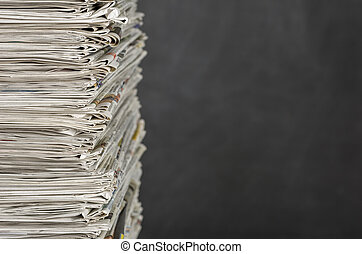 A pile of newspapers in front of a blackboard