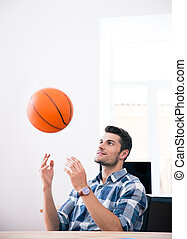 Happy businessman throwing ball in office - Happy...