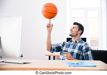 Happy businessman spining ball in office - Happy businessman...