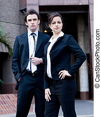 young adults - two young adults standing in busienss suits...