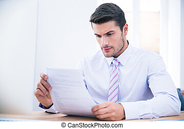 Businessman sitting at the table reading document - Handsome...