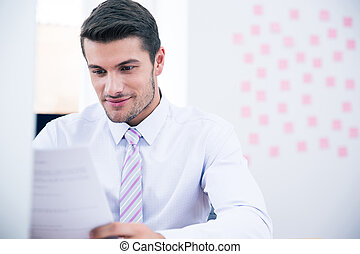 Businessman reading document in office - Handsome...