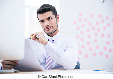 Happy businessman reading document in office - Happy...