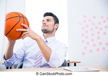 Businessman sitting at the table with ball in office