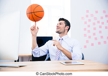 Smiling businessman spining ball in office - Smiling...