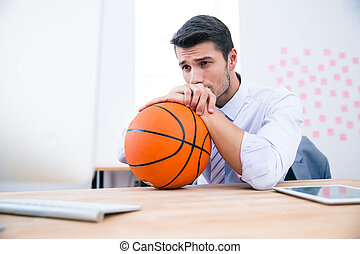 Pensive businessman sitting at the table with ball in...