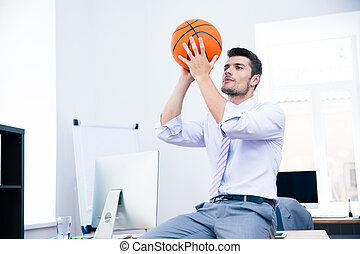 Businessman sitting on the table with ball - Formal...