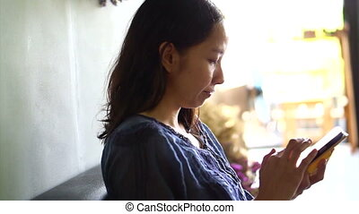 Asian girl using app on smartphone in coffee shop