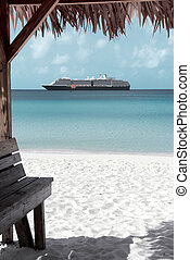 Caribbean sand beach with cruise ship at the background in...