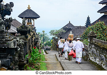 Balinese people walk in traditional dress in Pura Besakih -...