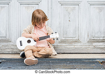 Little happy boy plays his guitar or ukulele, sitting by the...