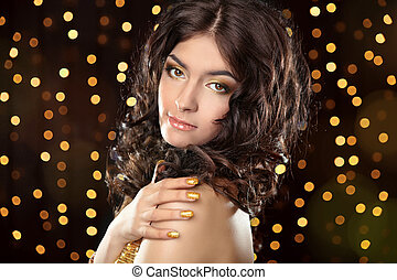 Young brunette girl with Long curly hair, beauty makeup, luxury jewelry. Beautiful attractive young woman in golden dress posing over holiday lights glitter background.