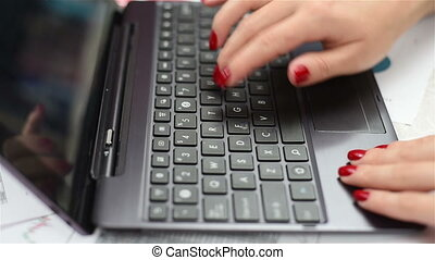 Woman hands working on laptop, close up