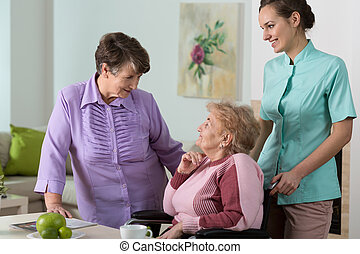 Friendly meeting - Two older women and young pretty nurse on...