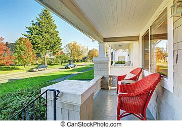 Covered patio with red chairs