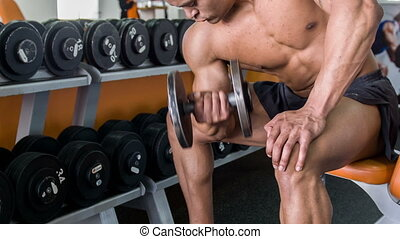 Attractive young man is exercising with heavy iron equipment