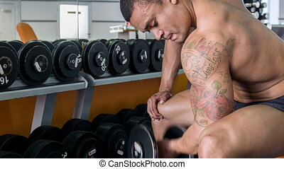 Handsome heavy-weight athlete is training with dumbbell -...