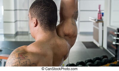 Fit young sportsman is raising heavy object in gym -...
