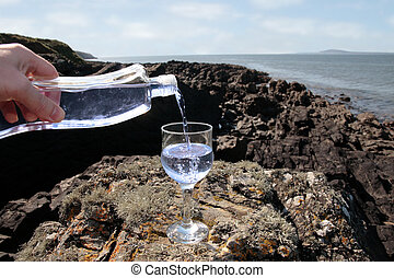 luxury drink - a glass of pure natural water being poured in...