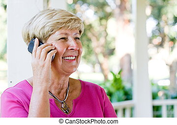 senior woman chatting - a senior woman happily chatting on...