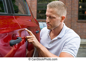 Man Looking For Scratches On His Car - Close-up Of A Young...