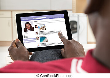 Man Chatting On Social Networking Site - Close-up Of African...