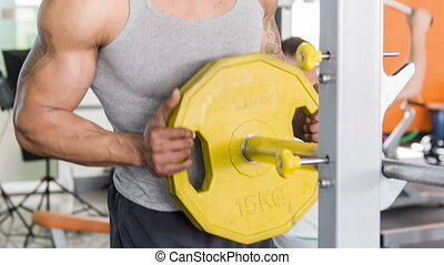 Handsome sportsman is adding weights on stand - Heavy-weight...