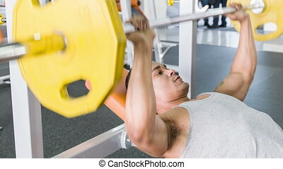 Strong beautiful athlete is lifting heavy weights
