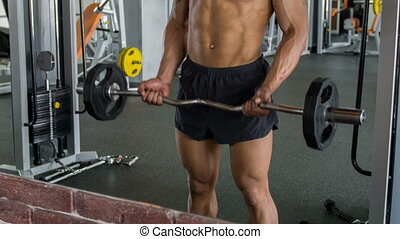 Handsome young athlete is lifting iron barbell