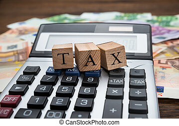 Tax Word On Wooden Blocks Over Calculator