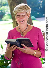 senior woman - a senior woman smiling with bible