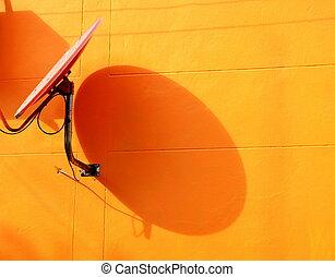 satellite dish on orange wall
