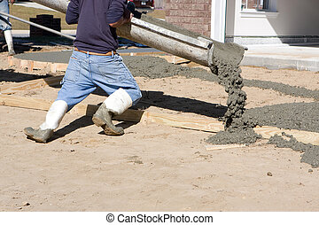 Man Pouring Concrete - Construction worker directing chute...
