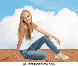 happy young woman in jeans and white tank top