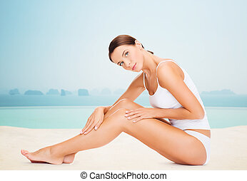 beautiful woman touching her legs - people, beauty, spa and...