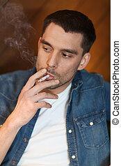 young man smoking cigarette at bar - people and bad habits...