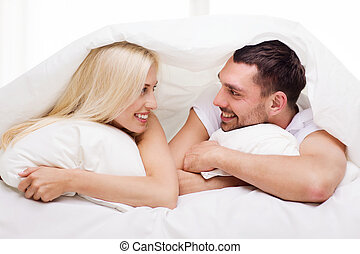 happy couple lying in bed and talking at home - people,...