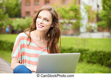 beautiful woman using a laptop outdoors - Young beautiful...