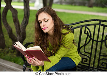 woman reading book at the park - Young woman reading book at...