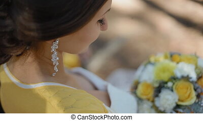 Bride look at her wedding bouquet - Young woman hold yellow...