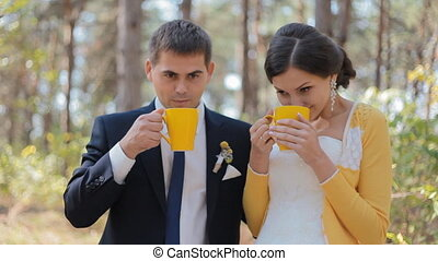 Young people drink tea outdoor Wedding photo session - Bride...