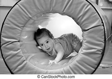Baby crawling through tunnel in indoor soft baby playground...