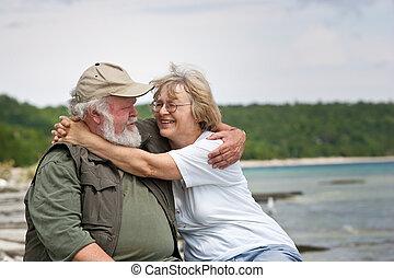 Senior couple sitting at shores edge - A senior couple...