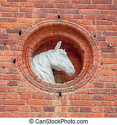 Horse head sculpture on a stables wall