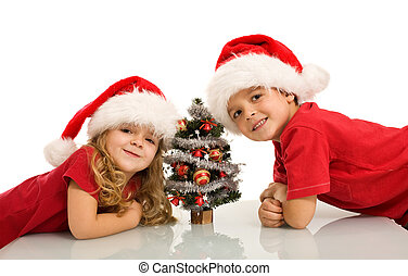 Happy kids with santa hats and small christmas tree -...
