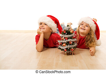 Happy kids with santa hats laying on the floor